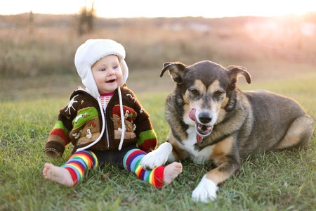 An adorable 8 month old baby girl is bundled up in a sweater and wearing a winter earflap hat looking lovinlgy at her pet German Shepherd dog as they sit and laugh ouside on a cold fall day.