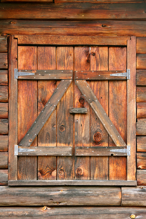 Close up of wood textured rustic window shutters on an old log home.