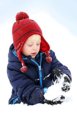 A 3 year old boy child is making bundled up in his winter hat and jacket, making a snowball in the deep white snow. 写真素材