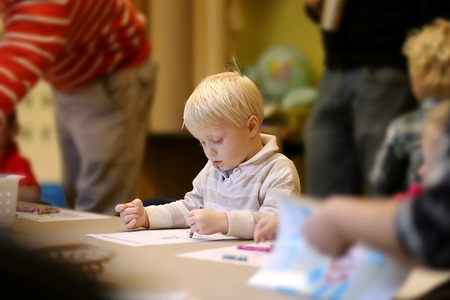 A cute 3 year old boy child is sitting quietly in Pre-K Sunday School class, coloring a picture, as teachers walk around behind him. Stock Photo