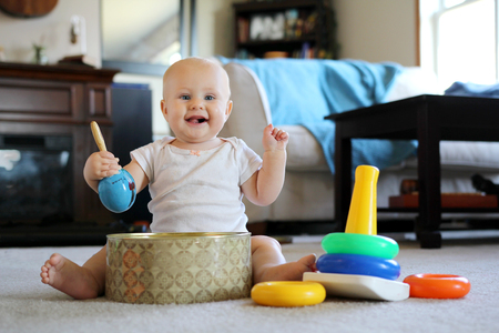 A happy smiling 8 month old baby girl is drumming with maracas and playing with donut stacking learning toys at her home.
