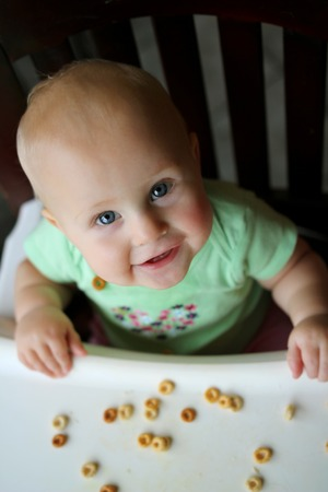 A happy 8 month old baby girl is smiling at the camera as she is sitting in her high chair eating hold grain finger food cereal. Imagens