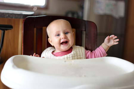 8 9 months: A very happy 8 month old baby girl with new teeth is smiling as she wears a bib and sits in her high chair at snack time. Stock Photo