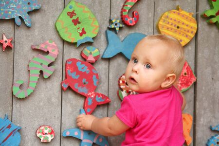 10 month: a cute 10 month old baby girl is standing up at a rainbow colored fish climbing wall at the playground. Stock Photo