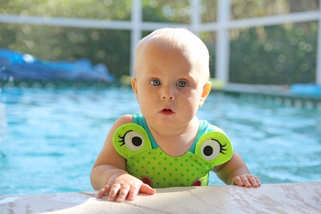 11 year old girl: A cute 10 month old baby girl is holding onto the ledge of a swimming pool and peeking at the camera.