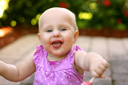 1 2 month: A super happy 10 month old baby girl with a messy face is laughing and sticking out her tongue while holding a popsicle outside on a summer day. Stock Photo