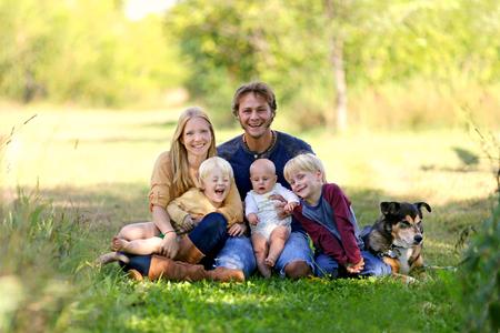 어머니, 아버지, 새로운 아기, 소년과 그의 형제를 포함하여 다섯 사람의 행복 한 가족들이 채택 독일 셰퍼드 강아지와 함께 햇볕이 잘 드는 정원에서