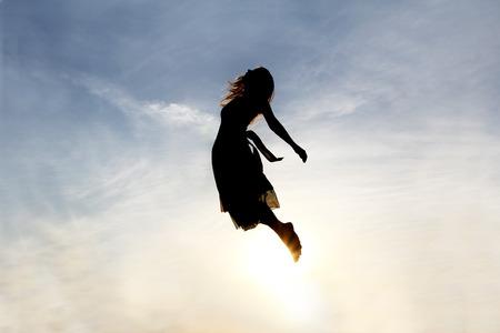 天国に送信されているかのように曇り空を背景に育った若い女性のシルエット。 写真素材