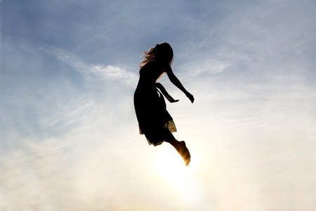 Silhouette of a young woman being raised into the cloudy sky background, as if being sent to Heaven. Stockfoto