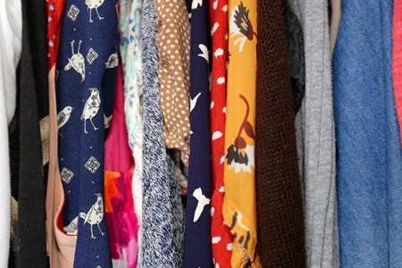 A variety of colorful women's clothing and dress of different fabrics, materials and patterns are hanging in the closet.