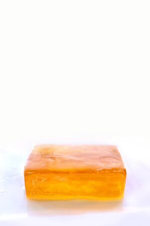 glycerin soap: An orange bar of glycerin face soap with suds on it is isolated on a white background, with empty room for copy-space