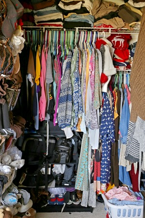 A messy closet is filled with trendy junior womans clothes in a variety of patterns and prints. Stock Photo