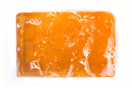 glycerin soap: An orange bar of glycerin face soap with suds on it is isolated on a white background. Stock Photo