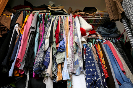 Un armario desordenado de las mujeres jóvenes es llenar con muchos equipos de ropa de colores, camisas, zapatos y vestidos. Foto de archivo