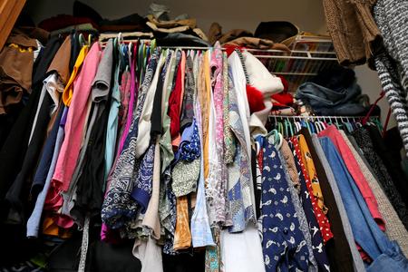 cuarto desordenado: Un armario desordenado de las mujeres jóvenes es llenar con muchos equipos de ropa de colores, camisas, zapatos y vestidos. Foto de archivo