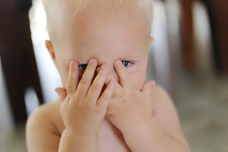 A one year old baby girl is covering her face with her hands and peeking through her fingers.
