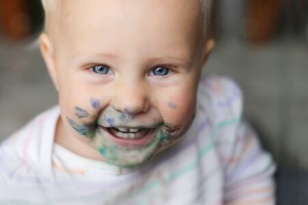 face covered: a happy, laughing one year old baby girl has a messy face covered in blue and purple paint. Stock Photo