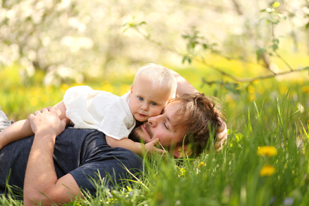 dad and daughter: A cute one year old baby girl is hugging her young father as they relax in a flowering apple tree orchard on a spring day. Stock Photo