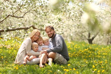 Een portret van een gelukkig gezin van vijf mensen, onder wie de moeder, vader, 2 jonge jongen kinderen en baby meisje hand in hand en knuffelen buiten in een bloem weide onder bloeiende appelbomen op een lentedag. Stockfoto - 60467999