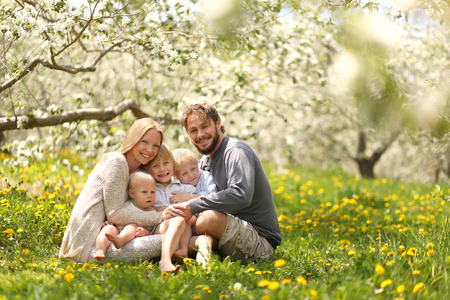A portrait of a happy family of five people, including mother, father, 2 young boy children and baby girl holding hands and hugging outside in a flower meadow under blossoming apple trees on a spring day.