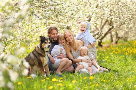 A portrait of a happy family of five people, including mother, father, 2 young boy children and baby girl and their pet dog hugging outside in a flower meadow under blossoming apple trees on a spring day.