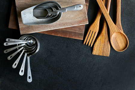 black boards: A collection of vintage baking and cooking supplies, wood cutting boards and spoons, and antique silver measuring cups frame a black slate chalkboard background.