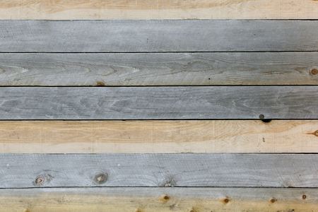 weathered: A background of textured rustic wooden plank boards that are knotted and weathered grey and tan brown.