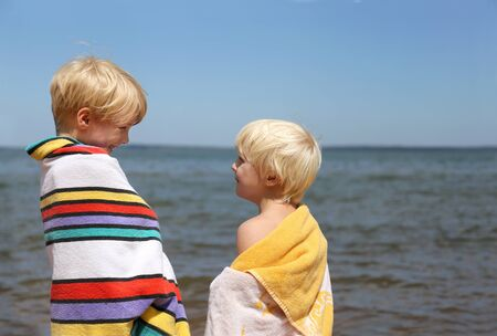 sun screen: Two happy little children, a six year old boy and his little brother, are smiling at each other as they stand on the beach of Lake Superior, wrapped in beach towels, on a summer day. Stock Photo