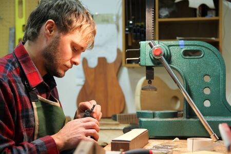 A young man in a flannel shirt is working as a luthier, using tools to building a guitar in his home workshop.
