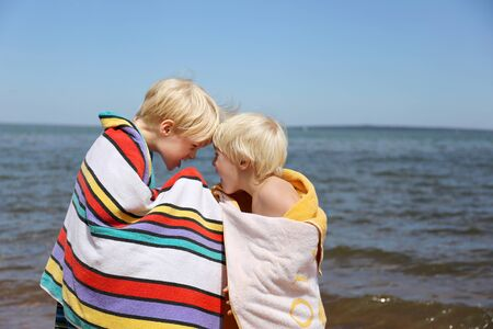 6 year old: Two young boys, a 6 year old child and his little brother, are making funny faces at each other while wrapped in beach towels and playing at the beach on a summer day.