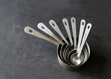 A Kitchen set of 6 silver measuring cups are nested inside each other on a black chalkboard background. Standard-Bild