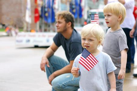 Dos jóvenes niños varones están agitando banderas americanas tal y como están con su padre en un desfile reloj acontecimiento patriótico en los Estados Unidos.