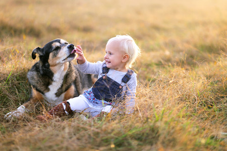 A rescued German Shepherd mix breed dog is licking the hand of a baby girl as she pets him outside on a fall day.