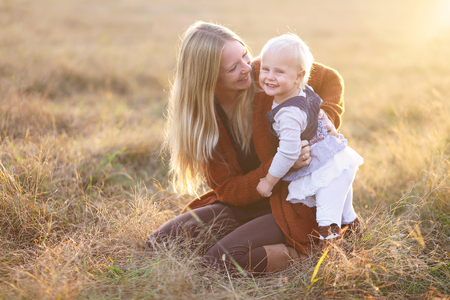 one year: A happy young mother and her one year old baby daughter are tickling and laughing outside in a field on a fall evening at sunset. Stock Photo