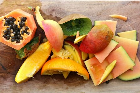 A variety of fruit skins and scraps on a wood cutting board, ready to be thrown in the compost pile in the garden.