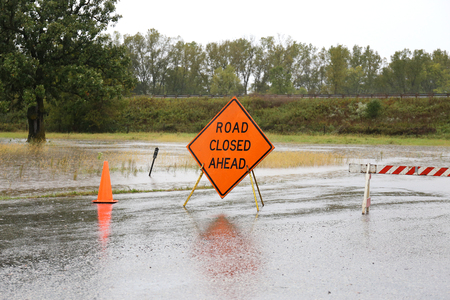 road closed: An oraange Road Closed Ahead Sign and Caution Cones are barricading a dangerous rain flooded street.