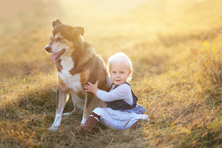 A happy one year old baby girl child is sitting in a farm field at the golden hour of sunset on a fall day, relaxing with her rescued german shepherd mix breed dog.
