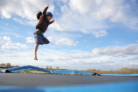 Un niño joven está saltando arriba mientras que juega en el patio en un trampolín familia grande, peligroso.