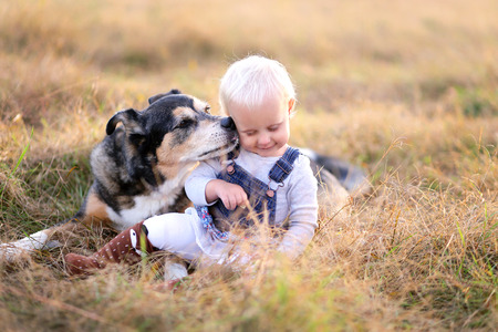 A German Shepherd mix breed dog is kissing his baby girl on the cheek as the relax outside at the golden hour on a fall evening.