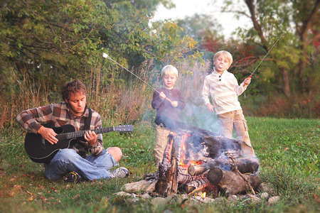 A father and his two young boy children are enjoying a campfire, playing guitar and roasting marshmallows on a fall evening. 免版税图像