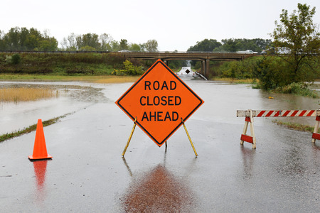 road closed: A bright orange Road Closed Ahead Sign and caution cones and barracades are blocking a rain flooded rural street.