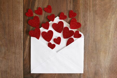 A blank white envelope is spilling out hearts from a Valentine's Day Love letter on a wooden cherry wood planked table. Reklamní fotografie - 70241658