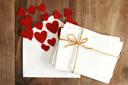 sobres de carta: A stack of blank envelopes ties with a twine string bow, are next to an open Valentines day love letter with red hearts flying out of it, on a rustic Cherry wood background.
