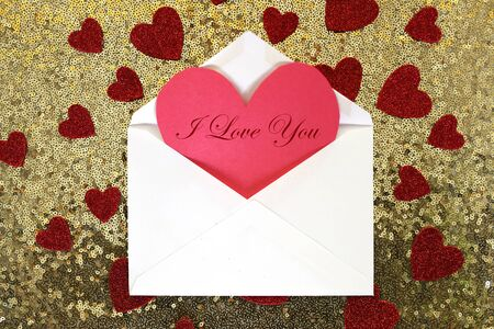 envelope: An envelope with a red Valentines day card in it with words i Love You  is on a gold sequin background, surrounded by sparkly heart confetti. Stock Photo