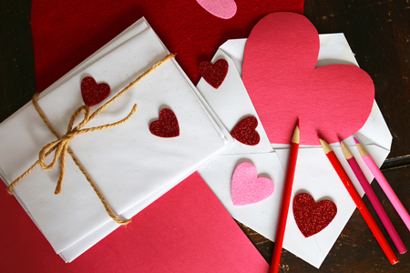 letter envelopes: Valentines Day Letter art supplies including: red and pink colored pencils, construction paper, heart shaped stickers, and a stack of envelopes with a twine string bow are sitting on a table.