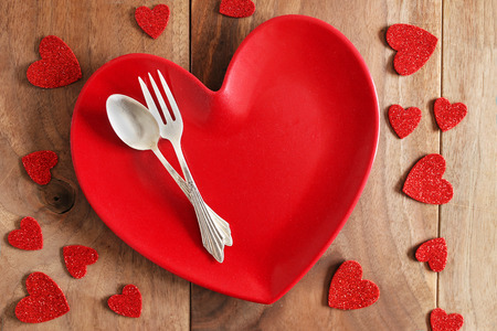 shaped: A red, heart shaped dinner plate with fine German silver fork and spoon, is on a rustic cherry wood planked table, surrounded by Valentines Day confetti.