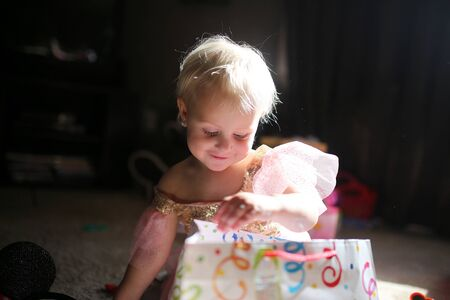 birthday presents: A happy little 2 year old baby girl wearing a princess dress is smiling as she opens birthday presents at her party. Stock Photo