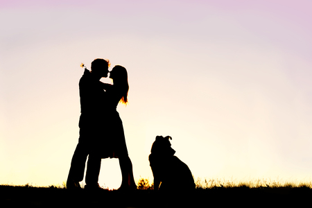 A silhouette of a happy young married couple in love, hugging at sunset next  to their pet dog outside on a summer night.