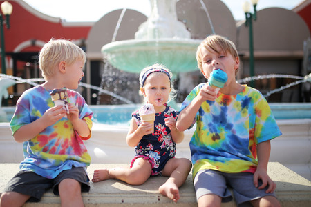 Three Young children, including 2 brothers and their baby sister, are sitting outside a restaurant on the patio, eating ice cream cones by a fountain. photo