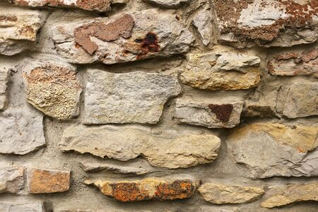 building exteriors: Close up on natural stone siding on the exterior wall of an old house. Stock Photo